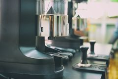 在酒吧柜台的电磨咖啡器机器在咖啡馆 免版税库存照片
