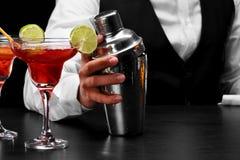 在酒吧柜台,玛格丽塔酒的一台振动器玻璃充分鸡尾酒,一位侍酒者的手黑色的弄脏了背景 免版税库存图片