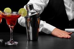 在酒吧柜台,玛格丽塔酒的一台振动器玻璃充分鸡尾酒,一位侍酒者的手黑色的弄脏了背景 免版税库存照片
