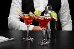 在酒吧柜台,金属发光的振动器的两块玛格丽塔酒玻璃,黑暗的一位侍酒者弄脏了背景 库存照片
