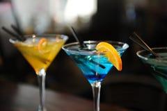 在酒吧的三个鸡尾酒 黄色,蓝色,绿色 用柠檬切片装饰 免版税库存照片