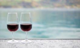 在酒吧的两块红葡萄酒玻璃在迷离绿化湖背景 免版税库存照片