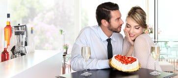 在酒吧的愉快的夫妇用香槟和草莓结块,爱 库存图片