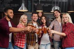 在酒吧的敬酒青年人的小组,举行啤酒杯,朋友欢呼站立在客栈的,愉快微笑 图库摄影