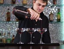 在酒吧的男服务员混合的鸡尾酒 库存照片