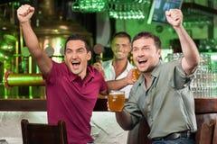 在酒吧的足球迷。欢呼在酒吧的两愉快的足球迷 库存图片