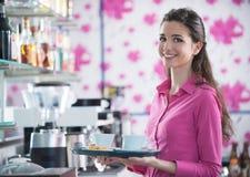 在酒吧的年轻微笑的女服务员服务咖啡 库存图片
