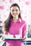 在酒吧的年轻微笑的女服务员服务咖啡 免版税库存照片