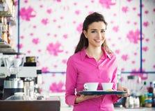 在酒吧的年轻微笑的女服务员服务咖啡 免版税图库摄影