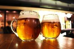 在酒吧表上的啤酒杯 库存照片