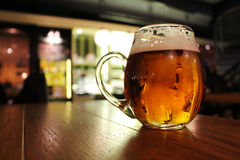 在酒吧表上的啤酒杯 免版税库存图片