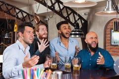 在酒吧饮用的啤酒,尖叫和观看橄榄球的混合种族沮丧的朋友的人小组 免版税库存图片