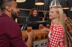 在酒吧,坐在木逆客栈,饮料啤酒的夫妇的青年人小组 免版税库存照片