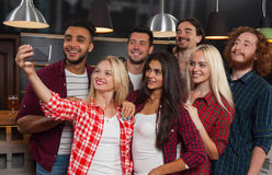 在酒吧,拍在细胞聪明的电话啤酒客栈的愉快的微笑的朋友的青年人小组Selfie照片 免版税库存图片