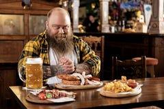 在酒店人的欲望肥胖男性品尝饭食 免版税库存照片