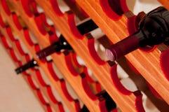 在酒机架的红葡萄酒瓶 免版税库存图片
