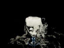 在酒杯的热水与在黑背景的烟 库存图片