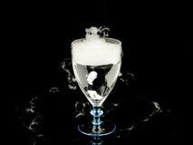 在酒杯的热水与在黑背景的烟 库存照片