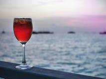 在酒杯的红色被冰的冷的饮料在木片断有公海和剪影小船日落背景  库存图片