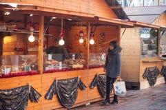 在酥皮点心立场前面的妇女在圣诞节市场上 免版税库存照片