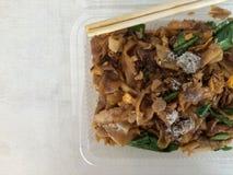 在酱油的油煎的面条在塑料盒和筷子在上面 免版税库存图片