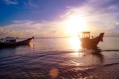 在酸值阁帕岸岛海滩的美好的日落与小船和明亮的太阳的,在泰国 库存照片