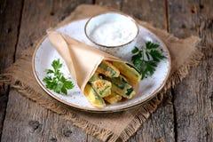 在酸奶、大蒜、莳萝、大蒜、盐和胡椒面团调味汁的油煎的夏南瓜  土气样式 库存照片