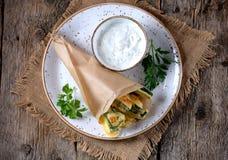 在酸奶、大蒜、莳萝、大蒜、盐和胡椒面团调味汁的油煎的夏南瓜  土气样式 免版税图库摄影