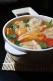 在酸蕃茄汤的煮沸的中国饺子 免版税库存照片