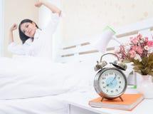 在醒的妇女转弯在床上以后 免版税图库摄影