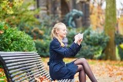 在采取与她的手机的巴黎街道上的美丽的少妇selfie 库存照片