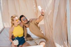 在采取与智能手机的太阳镜的愉快的年轻夫妇selfie 库存图片