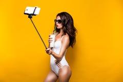 在采取与细胞的太阳镜和白色monokini的美好的深色的模型selfie在selfiestick,当喝鸡尾酒时 库存图片