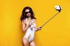 在采取与细胞的太阳镜和白色monokini的美好的深色的模型selfie在selfiestick,当喝鸡尾酒时 免版税库存照片
