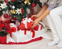 在采取当前箱子的妇女的特写镜头从圣诞树下面 库存图片
