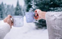在采取杯子热的饮料的编织的手套的男人和妇女手 图库摄影