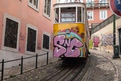 在里斯本葡萄牙小街道的黄色电车 库存照片
