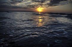 在里海和橙色天空的美好的燃烧的日落风景在它上与令人敬畏的在安静的太阳金黄反射挥动作为ba 免版税图库摄影