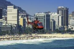 在里约热内卢,巴西抢救飞行在拥挤科帕卡巴纳海滩的直升机在热的夏日期间 免版税库存图片