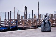 在重创威尼斯、的运河,长平底船和面具的清早 库存图片