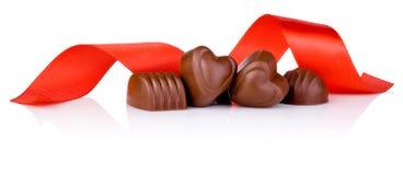 在重点形状和红色丝带的巧克力糖 免版税库存图片