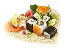 在重点芝麻的寿司塑造与绿色叶子 免版税库存照片