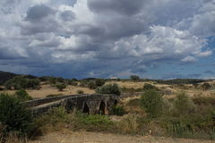 在重的云彩下的古老罗马桥梁 免版税图库摄影