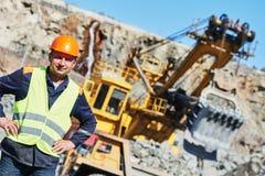在重的挖掘机和倾销者卡车前面的工作者 免版税库存照片