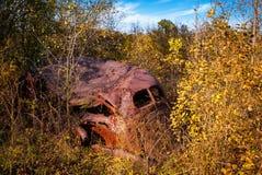 在重的杂草的老被放弃的生锈的古董车 库存图片