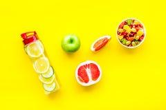 在重量白人妇女的美好的腹部概念损失 在果子柠檬和黄瓜水附近的水果沙拉在黄色背景顶视图 库存图片