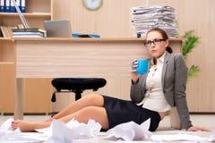在重音下的女实业家从许多工作在办公室 库存图片