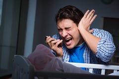 在重音下的年轻父亲由于哭泣在晚上的婴孩 免版税库存图片