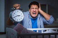 在重音下的年轻父亲由于哭泣在晚上的婴孩 免版税库存照片