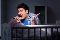 在重音下的年轻父亲由于哭泣在晚上的婴孩 免版税图库摄影